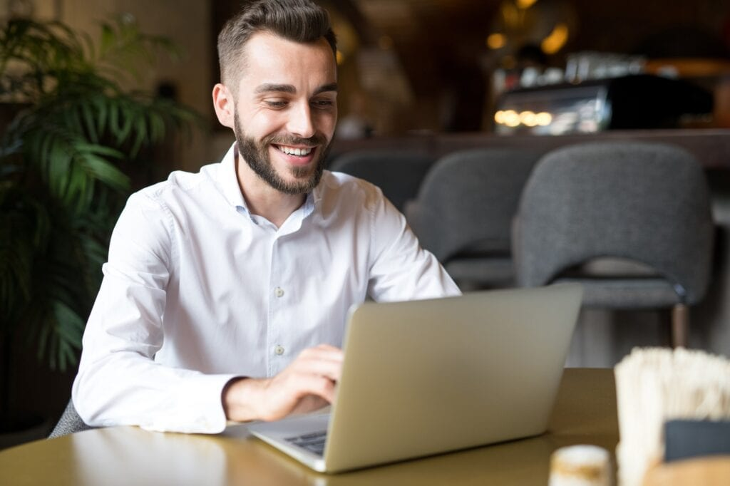 Cheerful Businessman Working in Cafe