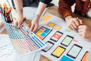 Cropped view of designers planning user experience design with color palette and website sketches on