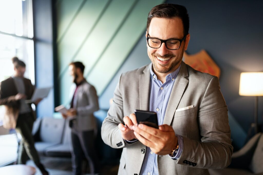 Handsome businessman checking emails on the phone in modern office