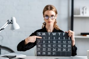 attractive businesswoman in black clothes and glasses holding calendar and showing date