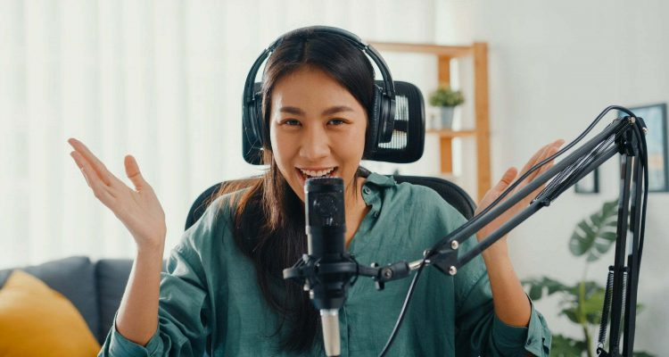 Happy asia girl record a podcast with headphones and microphone look at camera talk and take.