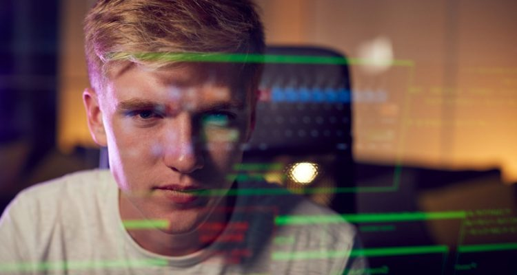 Male Teenage Hacker With Data Reflected From Computer Screen