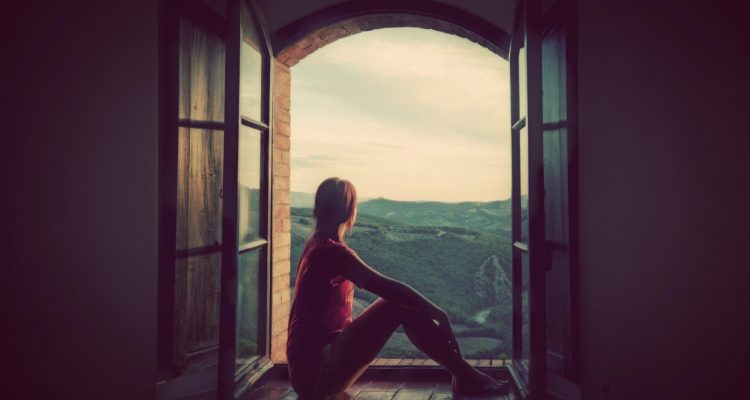 Young woman sitting in an open old window looking on the landscape of Tuscany, Italy.